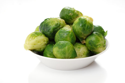 roasted brussels sprouts on a white plate, studio isolated